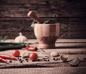 Mortar and pestle with pepper and spices on wooden table — Stock Photo