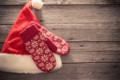 Santa's hat and red mitten on old wooden background — Stock Photo