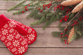 Red mitten, fir and berry on old wooden background — Stock Photo