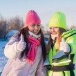 Two beautiful girls wearing warm winter clothes ice skating — Stock Photo #60028141