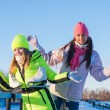 Two beautiful girls wearing warm winter clothes ice skating — Stock Photo #60028197