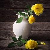 木製の背景に黄色のバラ — ストック写真