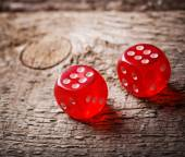 Pair of thrown red dices on old wooden table — Stock Photo