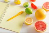 Citrus with notebook on white wooden table — Stock Photo