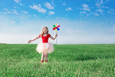 Girl  holding a toy flower on background sky and field — Foto de Stock