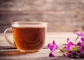 Cup of tea with willow-herb on wooden background — Stock Photo