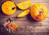 Pumpkin and pie on wooden table — Stock Photo