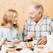 Grandfather and granddaughter sitting on the table in kitchen — Stock Photo #71892151