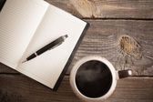 Notebook with pen and coffee on old wooden table — Stock Photo
