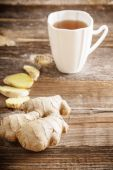 Ginger tea in a white cup on wooden background — Stock Photo