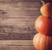 Three pumpkins on wooden background — Stock Photo