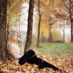 Beautiful elegant woman sitting in a park in autumn — Stock Photo #79353206