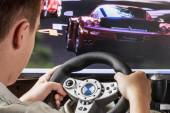 Teen playing in the race behind the wheel  — Stock Photo