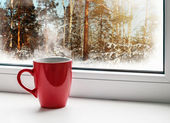 Red cup of coffee on windowsill — Photo
