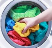 Hand puts laundry into the washing machine — Stock Photo
