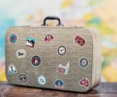 Old travel suitcase with badges — Stock Photo