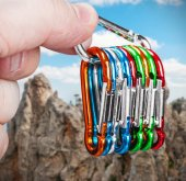 Colorful climbing carabiners  in hand — Stock Photo