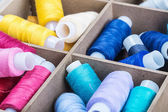 Multicolored threads in wooden box — Stock Photo