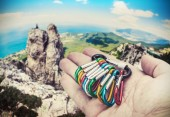Colorful carabiners for climbing in hand — Stock Photo