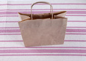 Brown paper shopping bag on a beautiful background — Stock Photo