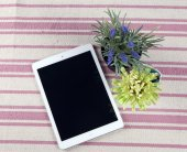 The composition of the tablet on a rustic rug with flowers — Stock Photo