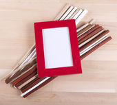 Beautiful composition with photo frames and fwooden sticks — Stock Photo