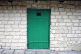 Old green door on the brick wall background. — Stock Photo