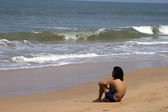 The Indian woman in a sari stones for building on the head on a beach. India Goa — Stock Photo