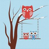 Christmas card with owls family sitting on the tree branch on blue knitted background. — Stock Vector