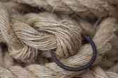 Coil of rope with a marine unit, and an iron ring. — Stock Photo