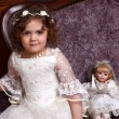 Little girl in dress sitting on chair — Stock Photo #70387977