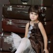 Girl sitting on retro suitcases — Stock Photo #70388613