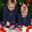 Girls sitting near Christmas fur-tree — Stock Photo #70389339