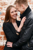 Young enamored pair a brick wall — Stock Photo