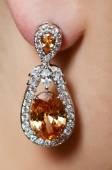 Female ear  in jewelry earrings — Stock Photo