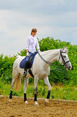 Girl on white dressage horse — Stock Photo