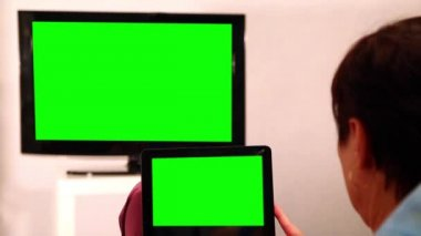 Woman With Green Screen Ipad Watches Tv — Stock Video