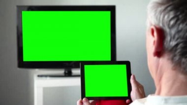 Man watches television while holding a tablet device. — Stockvideo