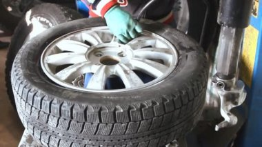 Mechanic removes car tire from disc closeup — Stock Video