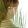 Pretty female behind palm leaf over white — Stock Photo #61029951