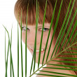 Pretty female behind palm leaf over white — Stock Photo #61029969