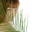 Pretty female behind palm leaf over white — Stock Photo #61029975