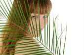 Pretty female behind palm leaf over white — Stock Photo