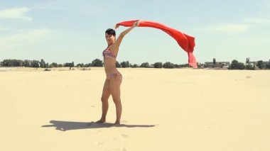 Young female with red sarong wind-blown standing on the beach — Stock Video