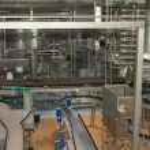 Plastic bottles on conveyor or water bottling machine — Stock Photo #76013107