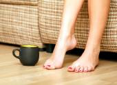 Female feet and a cup of tea or coffee — Stock Photo