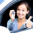 Happy girl in a car showing a key and thumb up gesture — Stock Photo #70929897