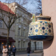 Ancient teapot on facade of old building in Vilnius, Lithuania. — Stock Photo #69488713