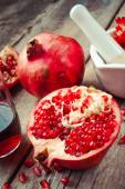 Pomegranate, juice in glass, mortar and pestle on wooden table — Stock Photo