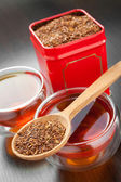 Rooibos in wooden spoon, two tea cups and tea tin box — Photo